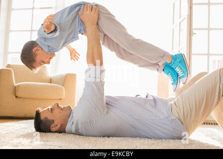 Side view of playful father lifting son while lying on floor at home - Stock Photo