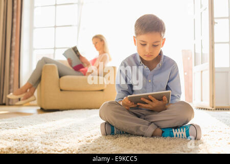 Boy using digital tablet on floor with mother reading magazine in background - Stock Photo