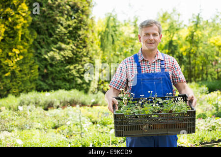 Portrait of confident man holding crate of potted plants at garden - Stock Photo