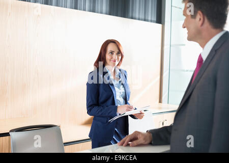 Businessman talking with receptionist in office - Stock Photo