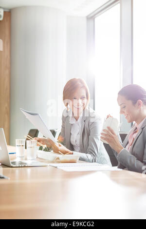 Young businesswomen having lunch at table in office - Stock Photo