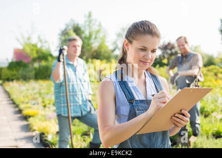 Beautiful supervisor writing on clipboard with gardeners standing in background at plant nursery - Stock Photo