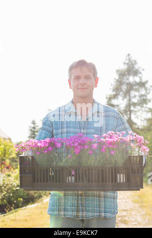 Portrait of man carrying crate with flower pots in garden - Stock Photo