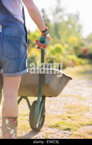 Midsection rear view of female gardener pushing wheelbarrow at plant nursery - Stock Photo