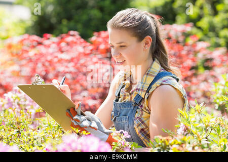 Female supervisor writing on clipboard in garden - Stock Photo
