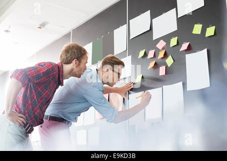 Businessmen analyzing documents on wall in office - Stock Photo