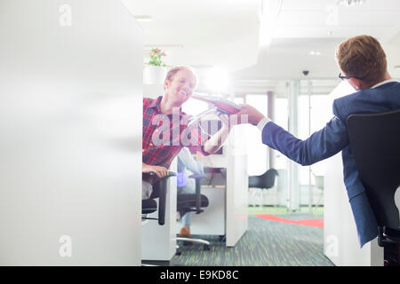Rear view of businessman giving files to colleague in creative office - Stock Photo