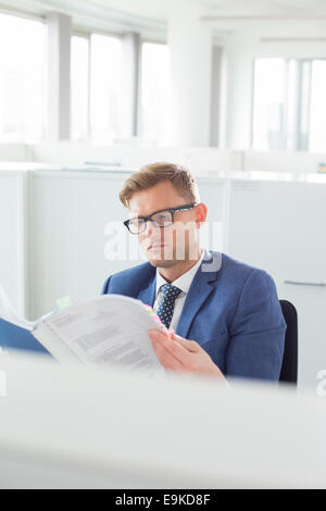Businessman reading file in creative office - Stock Photo
