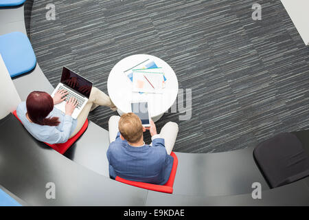 High angle view of business people using technologies in office - Stock Photo