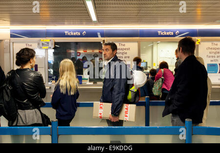 People waiting in a ticket queue on the London Underground, Kings Cross underqround station, London UK - Stock Photo