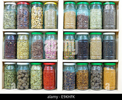 assortment of glass jars on shelves in herbalist shop in marrakesh, morocco, containing herbs and spices for medicinal - Stock Photo