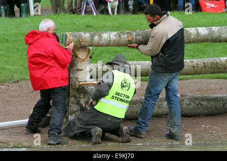 Stewards fix fence with a replacable frangable pin following damage to a fence at Mitsubishi Motors Badminton Horse - Stock Photo