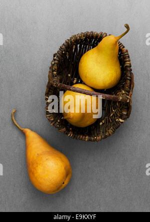 Three ripe pears in rustic basket over dark grey background - Stock Photo