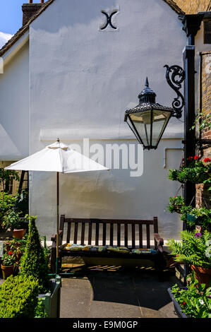 A cushioned bench against a plastered and painted building wall provides a comfortable place for a rest in an Elizabethan - Stock Photo
