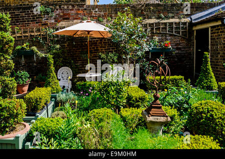 A white cast iron chair and table protected by a parasol provide a comfortable place to view the blooms in an Elizabethan - Stock Photo