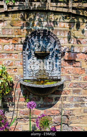 An old patterned cast iron fountain on the brick wall of an Elizabethan garden at the Six Poor Travellers' House, - Stock Photo