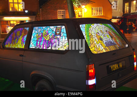 Stained glass car windows   Bicycle powered screens on Reliant Car an Exhibit at Illuminating King's Square York. - Stock Photo