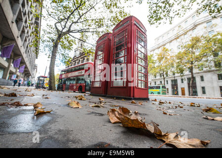 LONDON, UK - Autium leaves on the footpath in central London in front of a pair of red telephone boxes and a red - Stock Photo