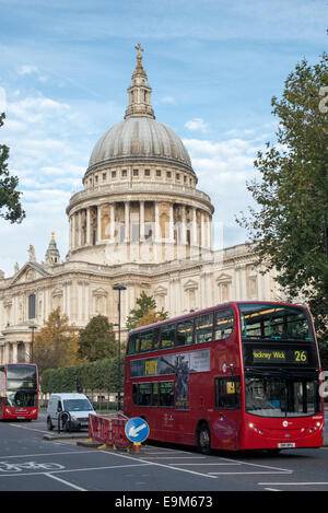 LONDON, UK - The iconic dome of St Paul's Cathedral in London, England, towers above the London buses below. - Stock Photo
