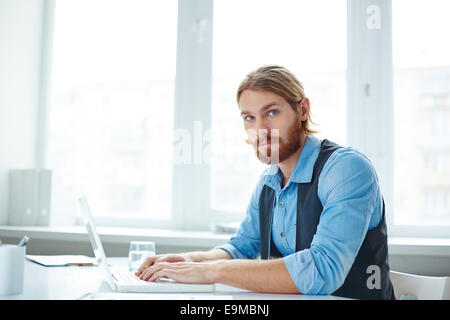 Young employee typing at workplace - Stock Photo