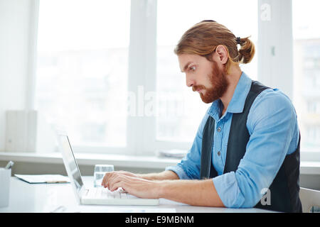 Serious businessman typing on laptop at workplace - Stock Photo