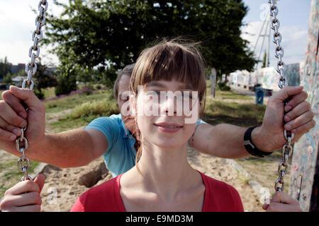 Man pushing woman on playground swing - Stock Photo
