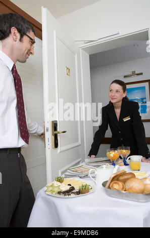 Woman delivering breakfast on push cart to businessman in hotel room - Stock Photo