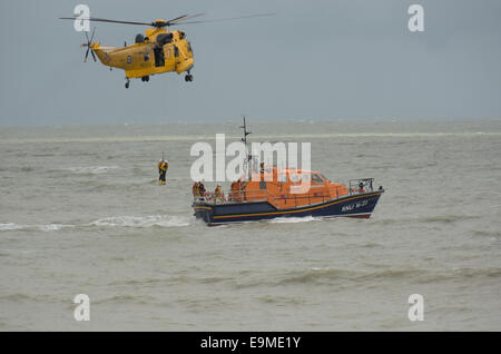A Royal Air Force Sea King helicopter completes a training exercise by returning two RNLI volunteers to the Eastbourne - Stock Photo