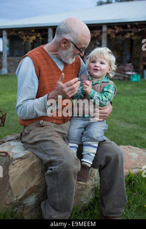 Cute boy sitting on grandfather's lap in park - Stock Photo