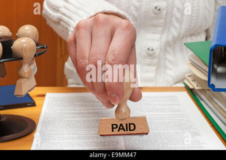 A stamp with the inscription paid is held in the hand - Stock Photo