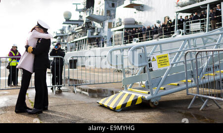 The crew look on as Captain Hugh Beard hugs wife Jenny on the quayside after the Type 23 frigate HMS Westminster - Stock Photo