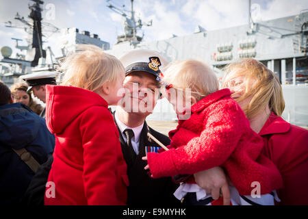 Chief Petty Officer Stuart Davidson receives kisses from daughters Alice, 4, and Lucy, 18 months, as wife Lise looks - Stock Photo