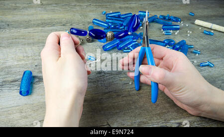 Woman's hands making a necklace from glass beads - Stock Photo