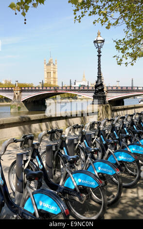 London, England, UK. Boris Bikes parked on the South Bank, Parliament and the Thames behind - Stock Photo