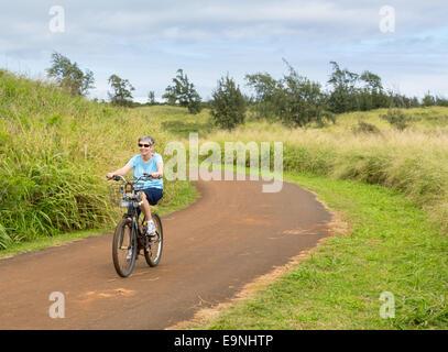 Senior lady on bike path in Kauai - Stock Photo