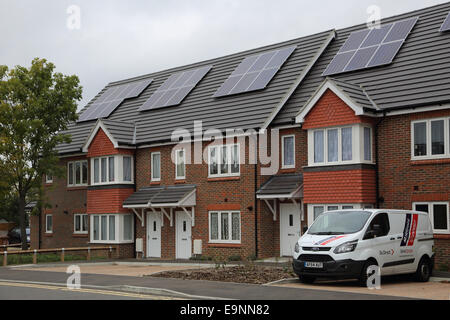 A new housing estate featuring solar PV panels installed on the pitched roof - Stock Photo