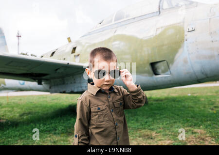 Little boy with sunglasses near the airplane - Stock Photo