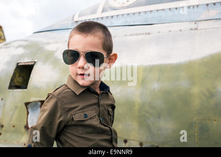Little boy with sunglasses sitting on the airplane - Stock Photo