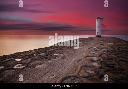 Lighthouse windmill with dramatic sunset sky. - Stock Photo