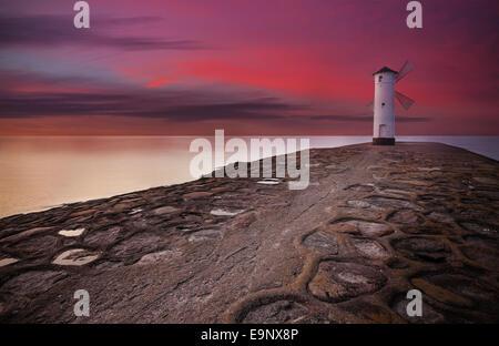 Stawa Mlyny Lighthouse windmill with dramatic sunset sky. - Stock Photo