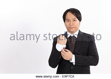Isolated of business man in suit correcting a sleeve - Stock Photo