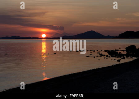 View of coastline with erupting volcano in distance at sunset, Sangeang Api (Mount Sangeang), Kelor Island, near - Stock Photo