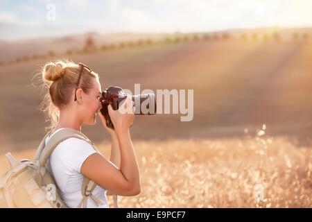 Happy traveler girl photographing ripe wheat field in bright sun rays, autumn harvest season, interesting profession - Stock Photo