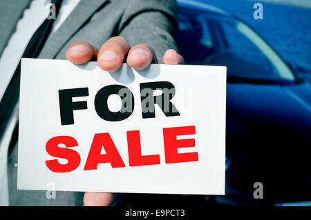 man in suit holding a signboard with the text for sale written in it, with a black car in the background - Stock Photo