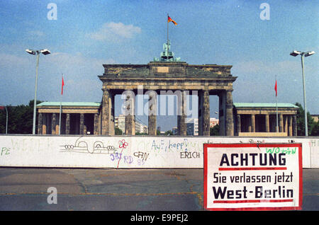 A sign in front of the Berlin Wall and Brandenburg Gate reads 'Achtung! Sie verlassen jetzt West-Berlin' (lit. 'Attention! - Stock Photo