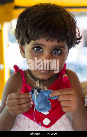 Portrait of young girl holding a toy in her hands. Jaipur, Rajasthan, India - Stock Photo