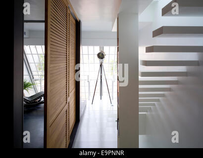 Cantilevered stairs and wooden louvered cupboard doors with spotlight on tripod in Hilit home, Israel. - Stock Photo