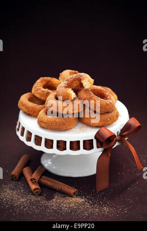 Donuts with cinnamon on cakestand; selective focus - Stock Photo