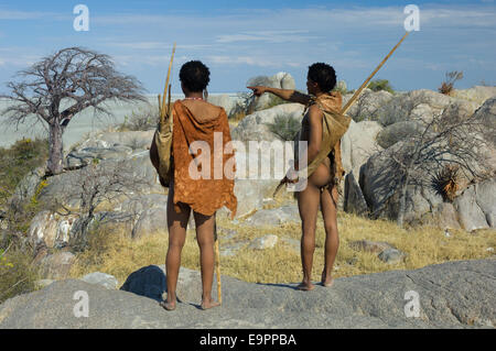 San Bushmen standing on the granite mass of Kubu Island (Lekhubu), looking out to the the Makgadikgadi Pan, Botswana - Stock Photo
