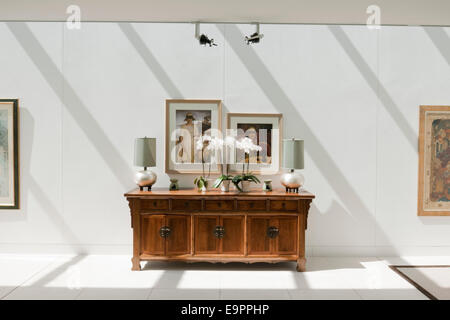 Wooden sideboard and framed prints in a modern space, UK home - Stock Photo